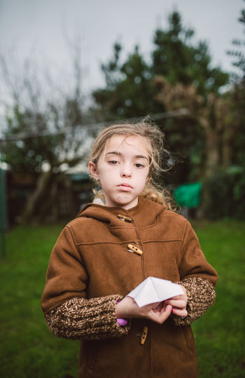 Portrait of girl holding origami while standing on land