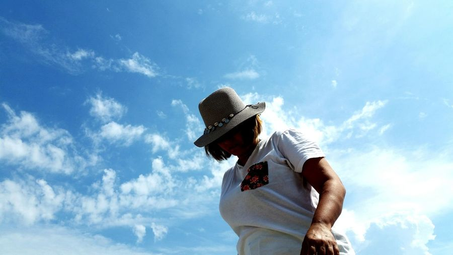 Low angle view of woman in hat standing against sky