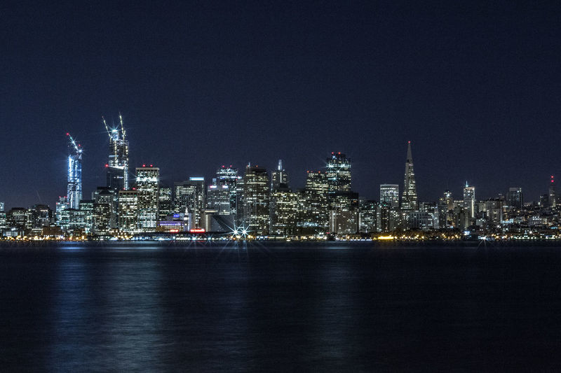 Illuminated cityscape by sea against clear sky at night