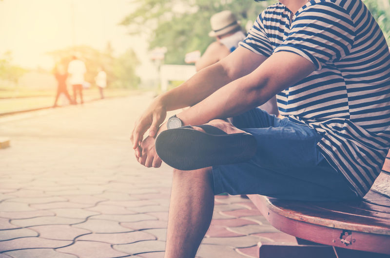 Low section of man with legs crossed at knee sitting on bench
