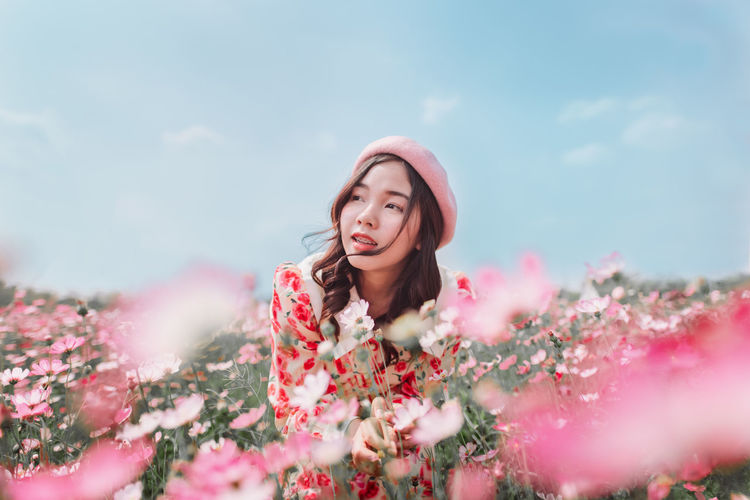 Woman with pink flowers against plants