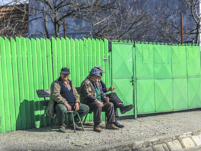 Old men sitting by the roadside in rural Romania. Sitting Full Length Seat Real People Tree Men Plant Nature People Day Bench Clothing Adult Lifestyles Relaxation Green Color Males  Hat Mid Adult Men Waiting Romania Three People