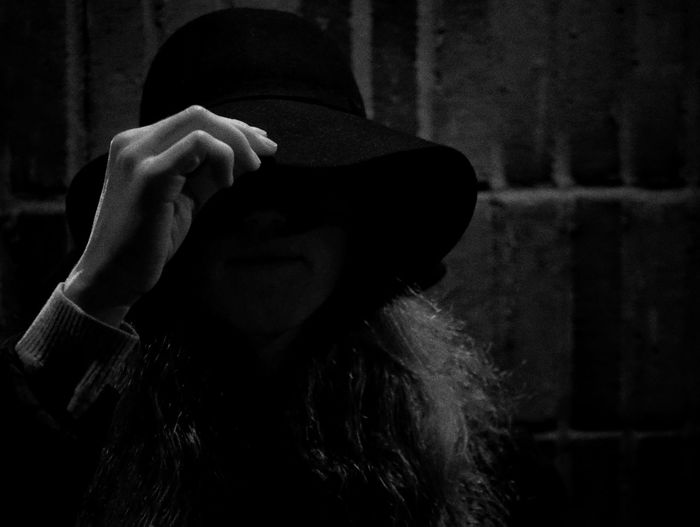 Close-up portrait of woman wearing hat against wall