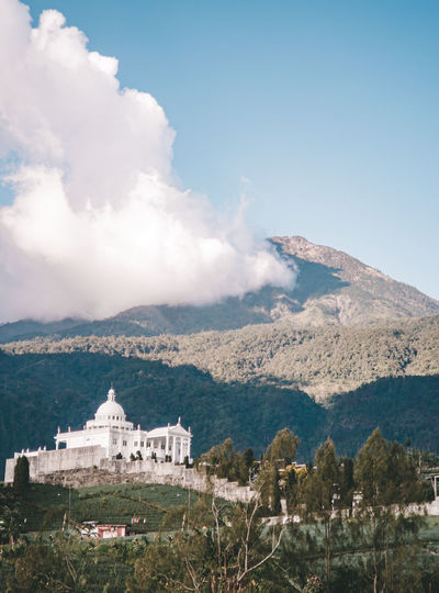 Buildings on mountain against cloudy sky