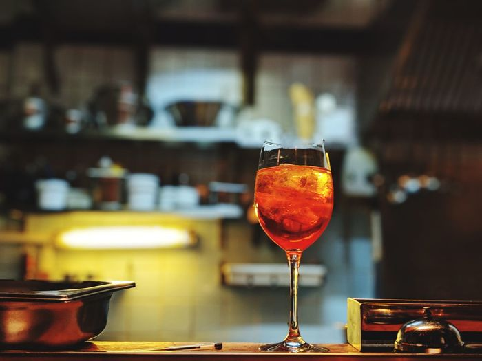 lonely Aperol on a counter Blurry Background Restaurant Countertop Wineglass Blood Orange Alcohol Drink Wine Drinking Glass Fruit Red Wine Close-up Food And Drink Aperitif Citrus Fruit