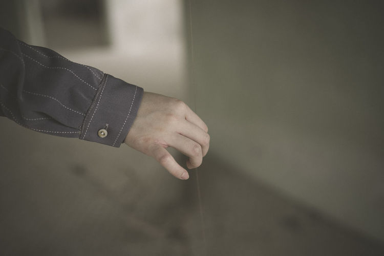 Cropped hand of man holding thread