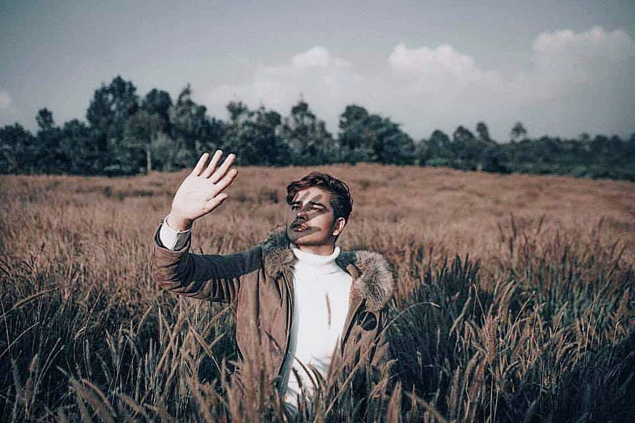 one person, field, plant, standing, young adult, nature, adult, landscape, land, grass, sky, tree, front view, emotion, portrait, human body part, happiness, day, outdoors, human arm, hand, arms raised