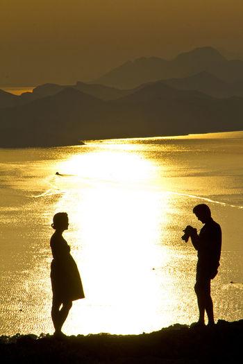 Full Length Of A Silhouette Couple On Beach
