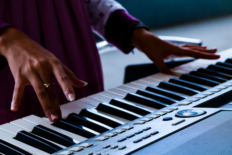 Cropped Image Of Woman Playing Piano