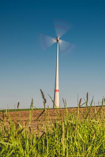Wind turbine in motion on field against clear blue sky