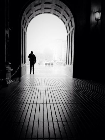 Silhouette man standing at archway