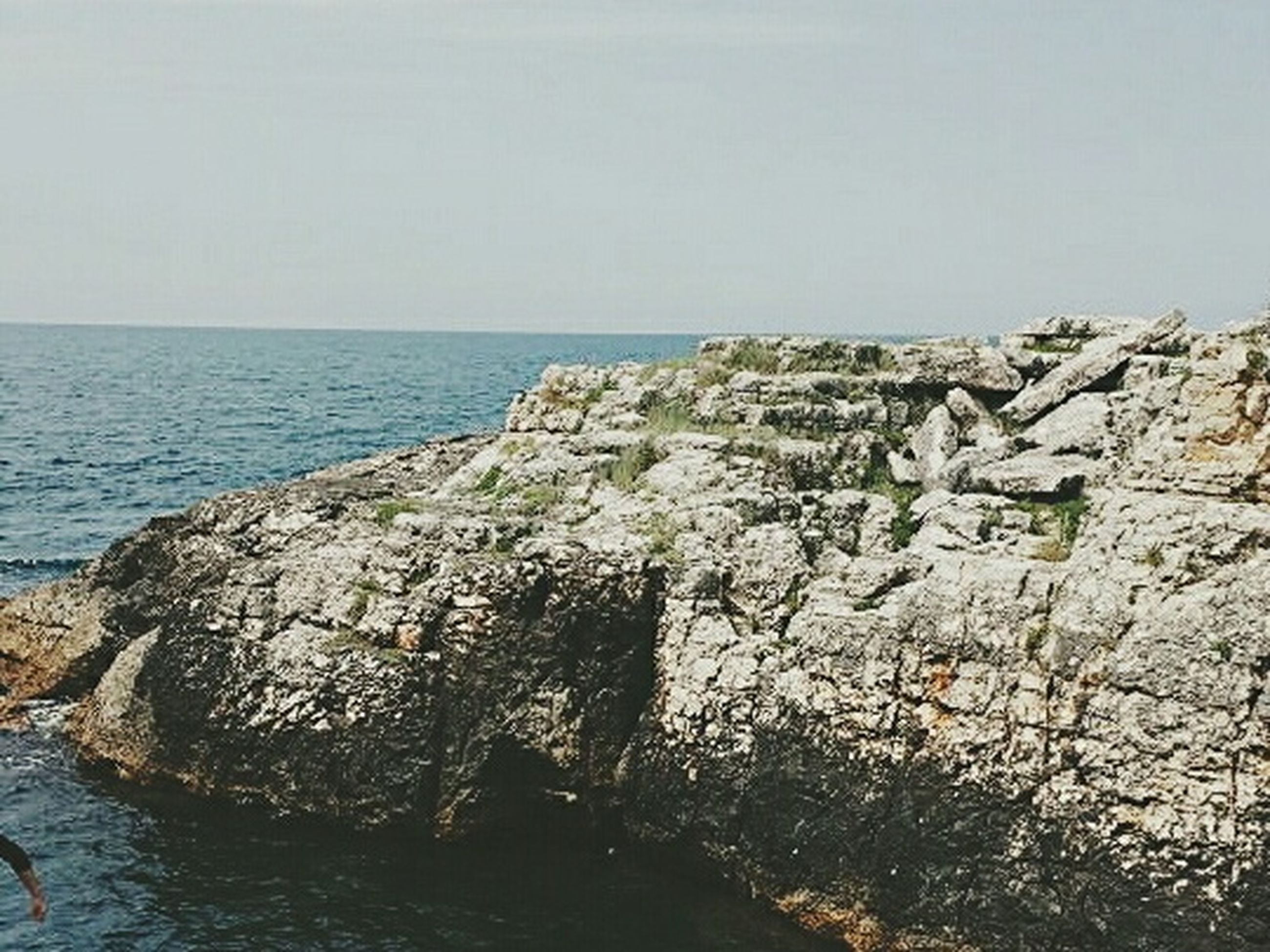 sea, water, horizon over water, rock formation, rock - object, clear sky, cliff, tranquil scene, scenics, tranquility, beauty in nature, nature, rock, copy space, day, coastline, idyllic, rocky, waterfront, sky