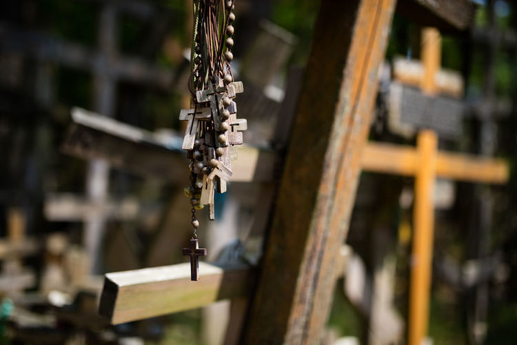Close-up of bead necklaces against cross at cemetery