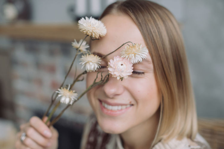 Close-up portrait of a smiling young woman holding flower