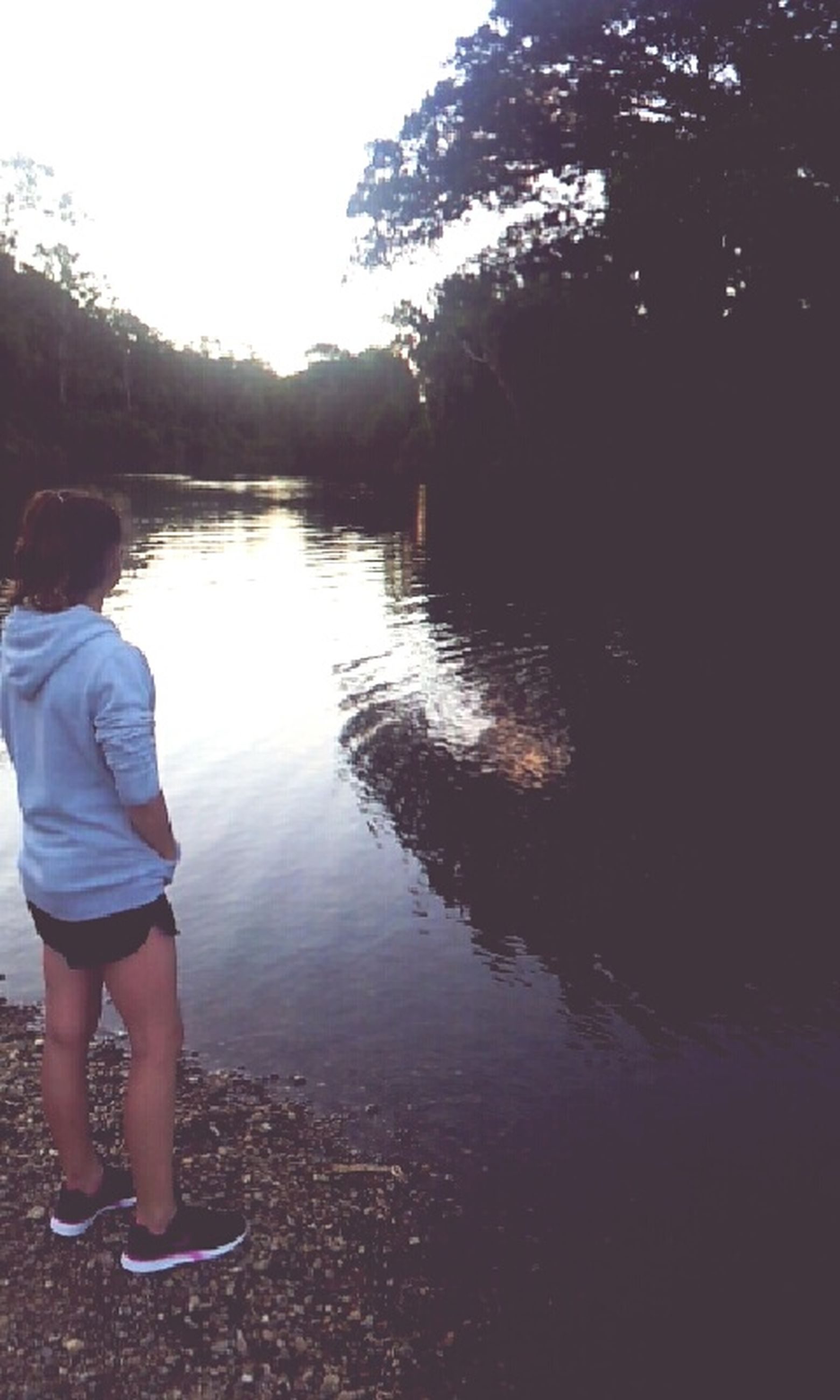 water, lifestyles, leisure activity, lake, rear view, casual clothing, standing, tree, tranquility, full length, tranquil scene, men, nature, reflection, scenics, river, beauty in nature, sky