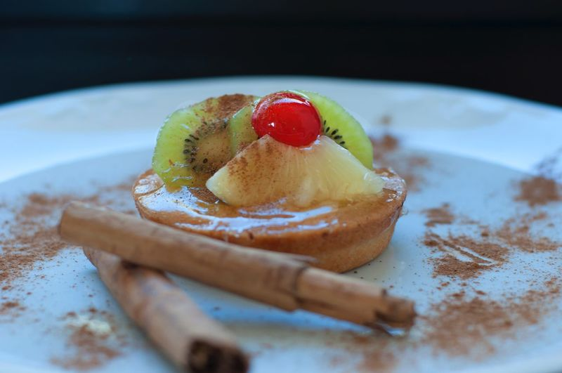 Close-Up Of Dessert With Fruits And Cinnamons In Plate