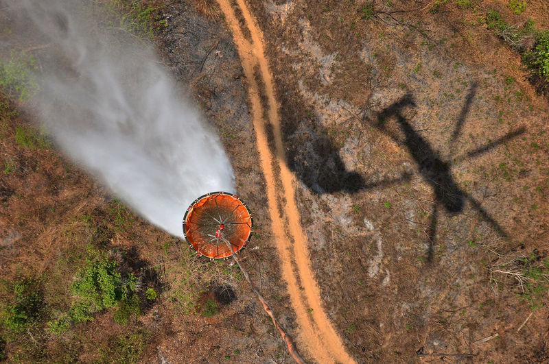 High Angle View Of Helicopter Pulling Container Over Landscape