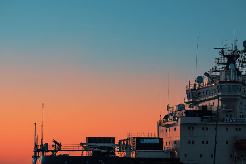 Ship moored at harbor against sky during sunset