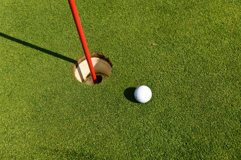 High angle view of golf ball reaching hole