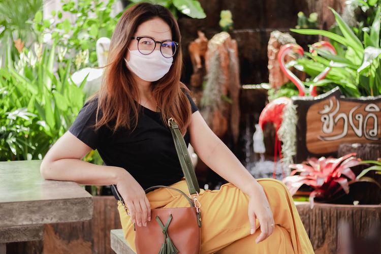 Portrait of woman wearing mask while sitting at cafe