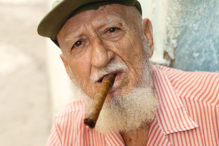 Close-up portrait of senior man wearing cap smoking cigar