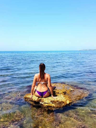 Rear View Of Young Woman Sitting On Rock At Beach