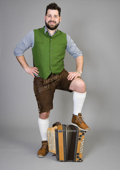 Musician Costume Leather Trousers Tradition Traditional Austria Green Pose Accordion Man Young Shorts Friendly Proud Happy Play Music Fun Joy Single One Background Copy Space Studio Entertainment Mountains Shirt STAND Hobby Leisure Cool Portrait Looking At Camera Studio Shot Full Length Front View One Person Indoors  Smiling Standing Casual Clothing Young Men Gray Background Young Adult Happiness Emotion Gray Beard Cut Out