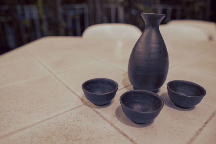 Close-up of pottery and cups on table