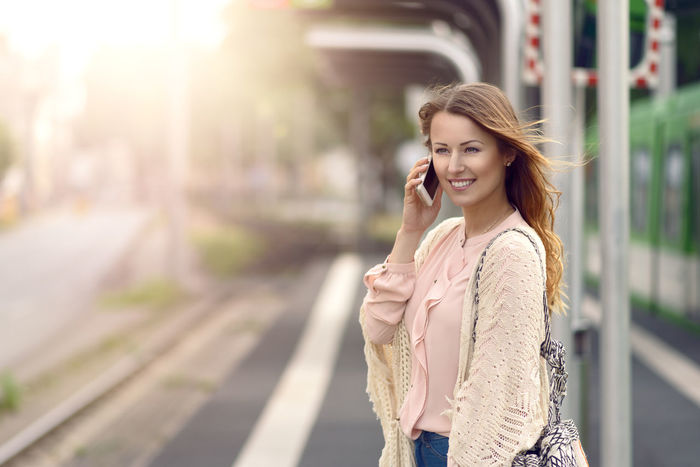 Attractive woman waiting on a platform Beauty In Nature Business Calling Cellphone City City Life Commuting Happiness Happy Listening To Music Morning Outdoors Platform Smart Phone Station Talking Train Station Urban Using Mobile Waiting Woman Ypung