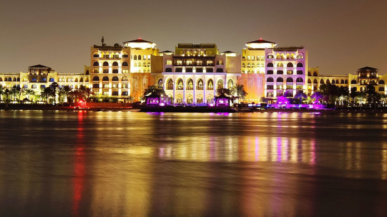 ILLUMINATED BUILDINGS IN FRONT OF CANAL IN CITY