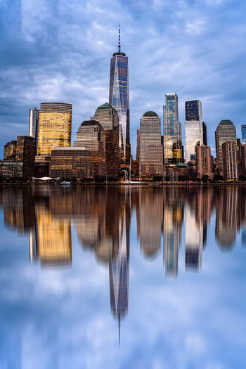 Financial district of NYC and reflection on water of Hudson river at dusk Cityscape Financial District  Hudson River NY NYC New York Reflection Architecture Building Building Exterior Built Structure City Cityscape Cloud - Sky Dusk Financial District  Landscape Modern Nature Night No People Office Building Exterior Reflection River Sky Skyscraper Spire  Sunset Tall - High Tower Travel Destinations Urban Skyline Water Waterfront