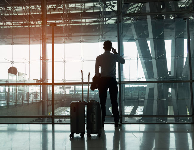 Business man use smart phone. Real People Full Length Travel Men Indoors  Transportation Glass - Material Airport Luggage Day One Person Window Transparent Rear View Architecture Standing Mode Of Transportation Lifestyles Silhouette Airport Departure Area Airport Terminal Waiting