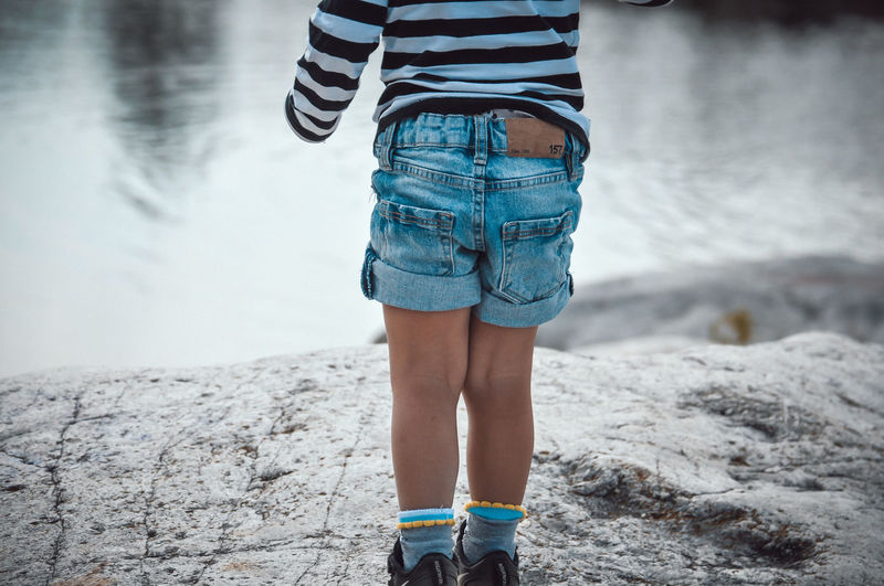Low section of child standing on beach