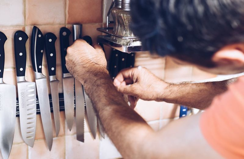 Close-up of man picking knife at home