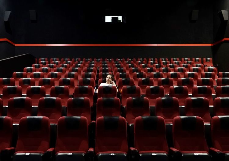 Rear view of people sitting in empty chairs
