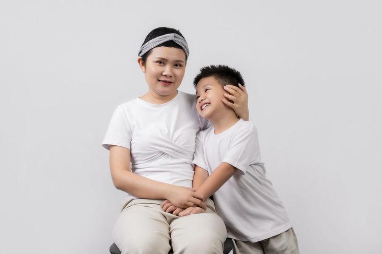 Smiling boy sitting against white background