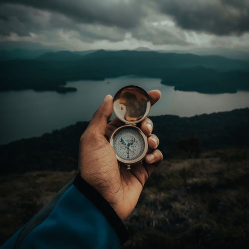 Midsection of person holding compass against mountain