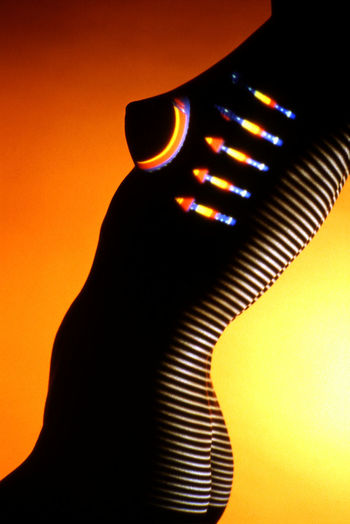 Close-up of silhouette hand on illuminated light