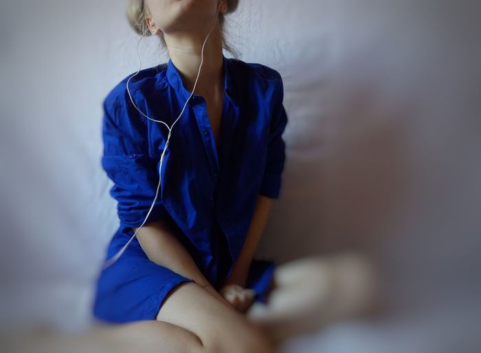 Midsection of young woman listening music while sitting on bed