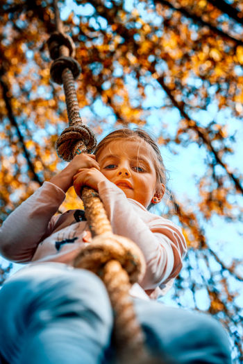 Low angle view of girl swinging against trees