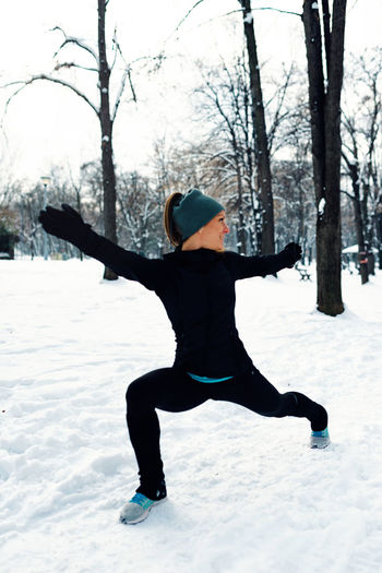 Woman Exercising On Snowy Field Against Bare Trees