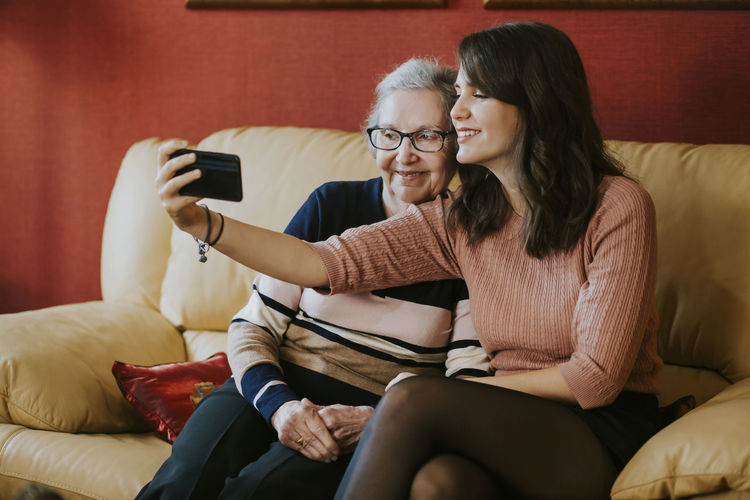 Woman using mobile phone while sitting on sofa