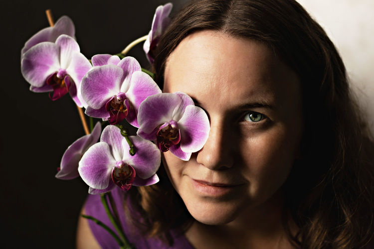 Portrait of a young woman in a purple dress with a blooming orchid. a flower covering one eye