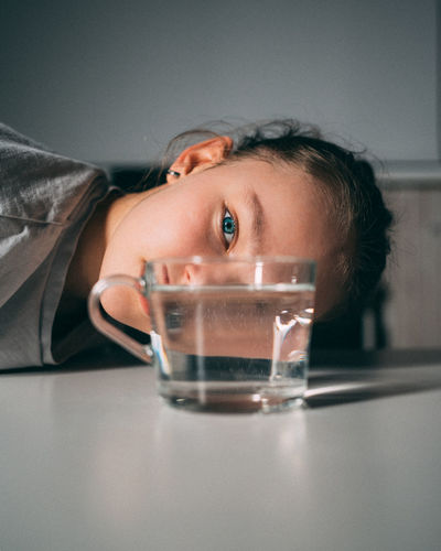 Portrait of boy drinking water from glass on table