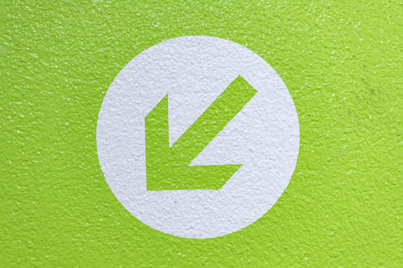 Close-up of arrow sign on green background