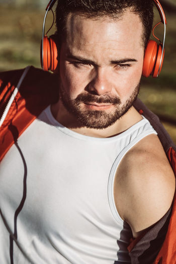 Close-up of young man wearing headphones looking away outdoors