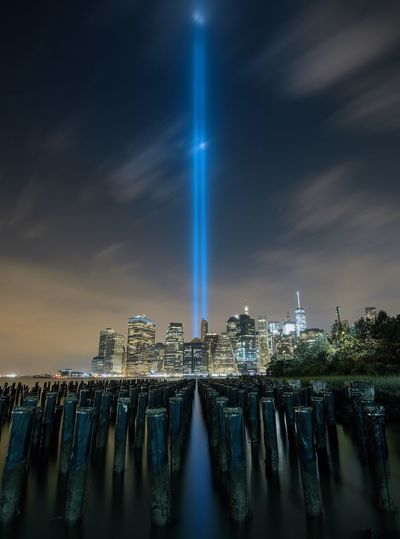 Wooden post in east river against light beams symbolizing world trade center in city against sky at night