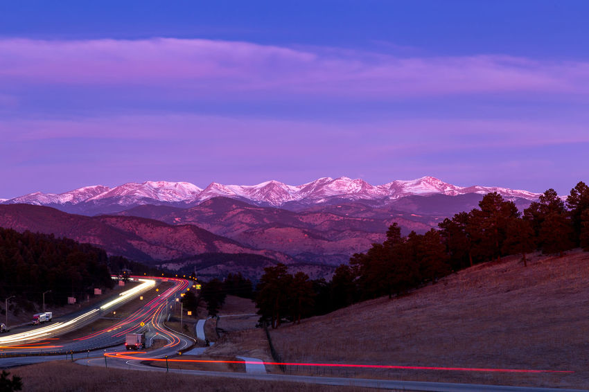 A group of mountains at sunrise. The highway and the lights of the cars create a leading line through the scene. Leading Lines Light Trails Morning Beauty In Nature Dawn Illuminated Landscape Light Trail Mountain Mountain Range Nature Night No People Outdoors Road Scenics Sky Snow Snowcapped Mountain Speed Sunrise Transportation Tree Winding Road Winter