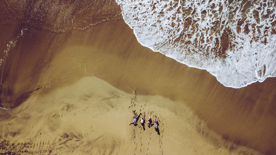 High angle view of friends lying at beach
