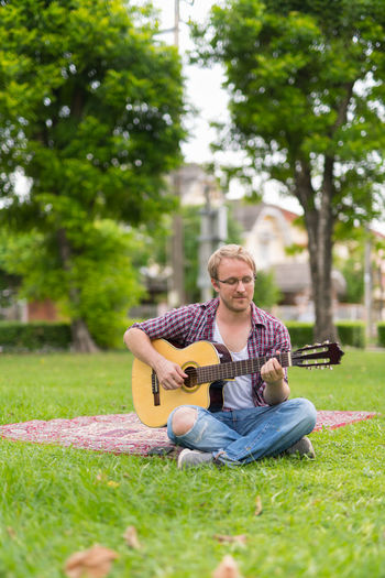 Young man playing guitar in park